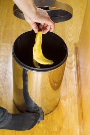botes de basura: Foto vertical de la piel femenina plátano puesta en bote de basura con pisos de roble amarillo en el fondo