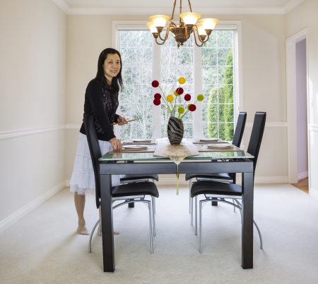 photo of mature woman placing bamboo chopsticks on place mats in family formal dining room with daylight coming through large windows in background Stock Photo - 18230413