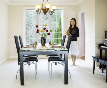 photo of mature woman bringing tea into family formal dining room with daylight coming through large windows in background Stock Photo - 18230414