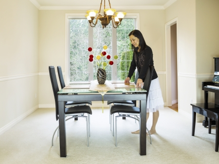 Photo of mature woman placing diner mats in family formal dining room table with daylight coming through large windows in background Stock Photo - 18230415