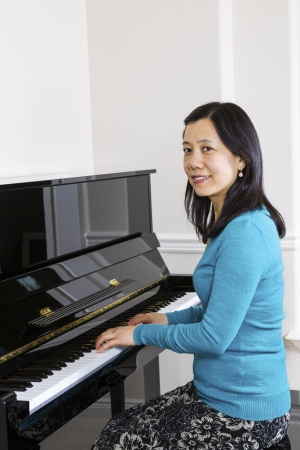 asian art: Vertical photo of mature woman playing piano with white walls in background Stock Photo