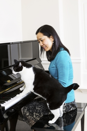 Vertical photo of mature woman watching her family cat with his paws on the keyboard of the piano  photo