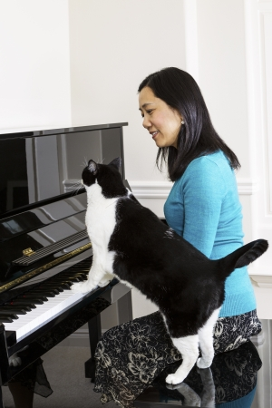 Vertical photo of mature woman playing piano with family cat at her side  photo