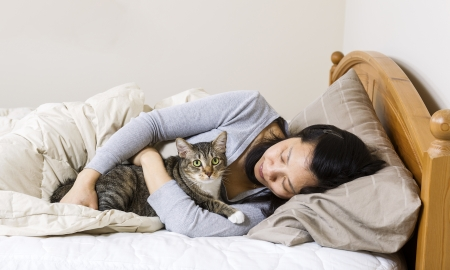 Horizontal photo of mature woman, lying head down in pillow, while hold her family cat in bed  Stock Photo