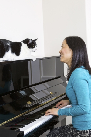 Vertical photo of mature woman with her family cat on top of piano looking at each other while sitting at the piano  photo