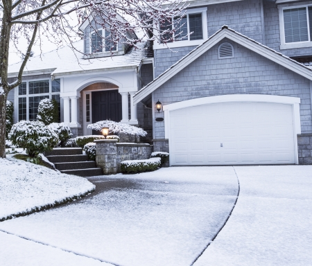photo of suburban home with snow on drive way, lawn, plants, trees and roof  Stock Photo