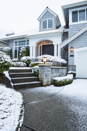 Vertical photo of side walk leading to suburban home with snow on ground