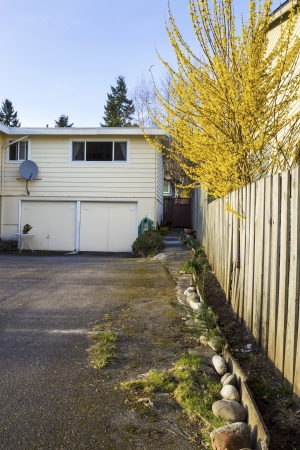 two car garage: Vertical photo of older residential home, in early spring, with long driveway leading to two car garage  Stock Photo
