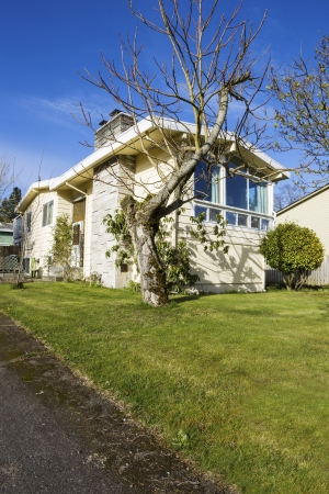 Vertical photo of older residential home in early spring with partial front yard, driveway, bare trees and blue sky Stock Photo - 18658438