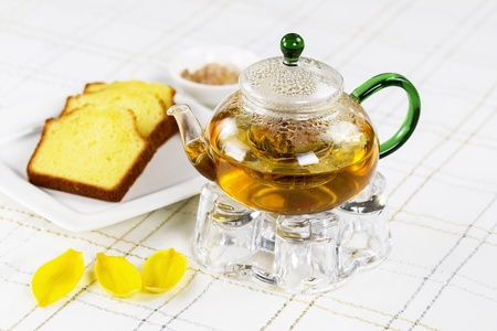 yellow tea pot: Horizontal photo of glass tea pot, holder, sugar in bowl, yellow flower leafs, and lemon pound cake with White Striped Table Cloth in background