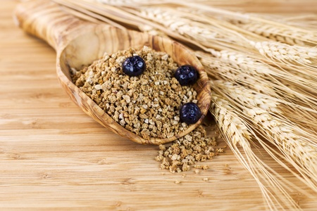 Closeup of horizontal photo of wooden spoon filled with Whole Grain Cereal with blueberries on top, wheat stalks on side Stok Fotoğraf