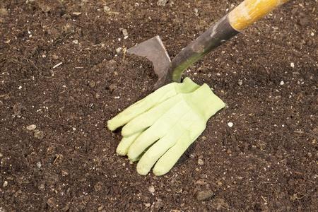 Horizontal photo of garden shovel in soil with work gloves next to blade  Stok Fotoğraf
