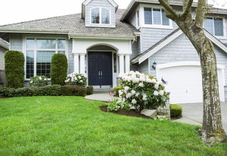 중반 봄 시즌에 플러시 푸른 잔디, 진달래와 튤립 꽃 북미 교외에 현대 홈