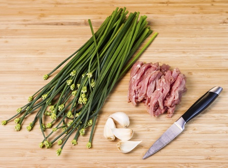 paring: fresh Chives with buds, raw lean pork, garlic cloves, and paring knife on natural wood