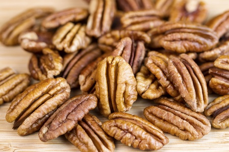pecan: slightly roasted pecan nuts with focus of standing pecan in front of pile on natural wood  Stock Photo