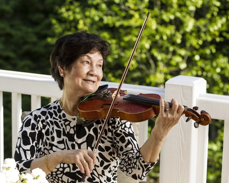 senior asian: Horizontal photo of Senior Asian woman sitting down while playing the violin outdoors with green trees in background