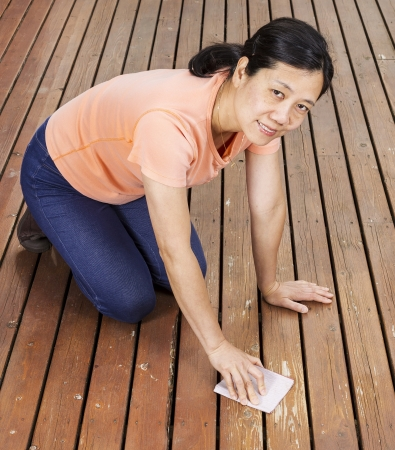 Photo of mature woman hand sanding a natural faded cedar wood deck while smiling  photo