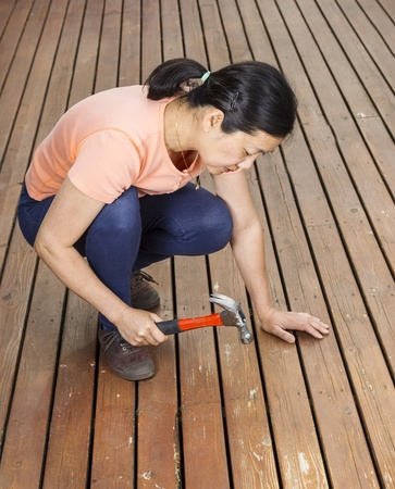 Vertical photo of mature woman adjusting boards, with hammer in raised position, on a natural faded cedar wood deck  photo