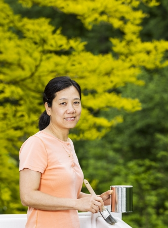 Vertical photo of a mature woman holding paint can and brush while preparing to work on white wood deck railing with a green nature background photo