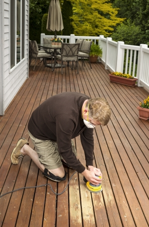 Vertical photo of mature man kneeling while sanding outdoor wooden cedar deck with patio furniture and trees in background  Stock Photo