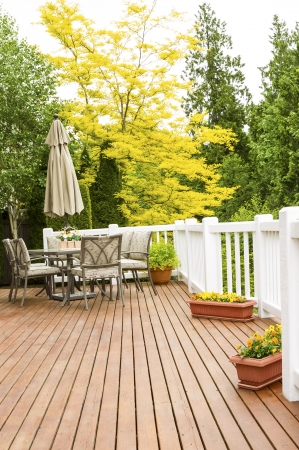 deck: Vertical photo of a large outdoor natural cedar deck with patio furniture and bright yellow and green trees in background Stock Photo