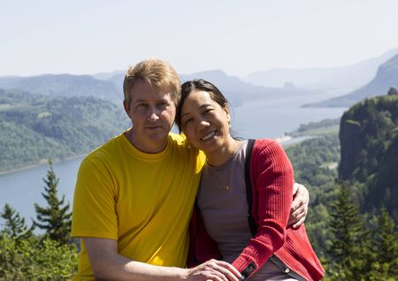 interracial marriage: Horizontal photo of mature interracial couple holding each other with the Columbia River Gorge located in the Northwest section of the United States in the background  Stock Photo