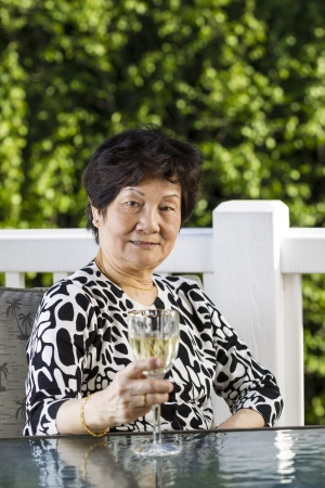 Vertical photo of senior Asian woman drinking white wine on a nice day with white patio railing and plush green trees in the background photo