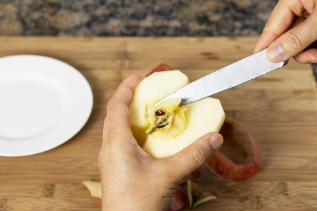 paring: Horizontal photo of female hands removing pit of freshly peeled apple using a paring knife with bamboo cutting board, white dish and stone counter top in background