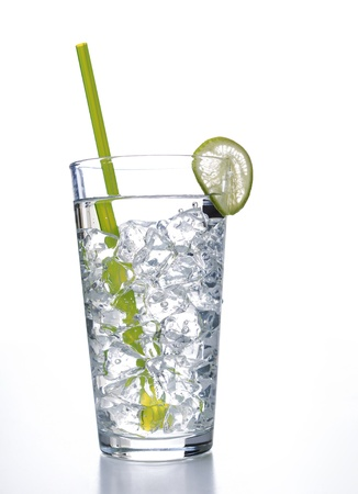 Vertical photo of a tall glass of water with ice cubes, slice of lime and a green straw on a white background Banco de Imagens