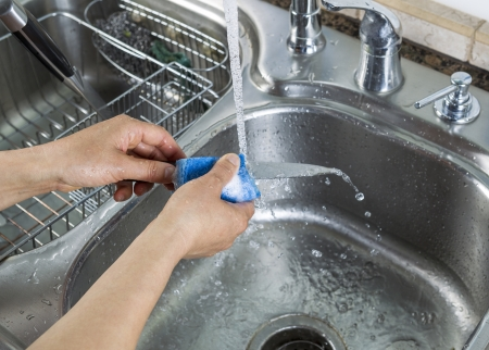 photo of female hands washing a small knife with a soapy sponge with kitchen sink and running faucet in background Stock Photo - 20145980