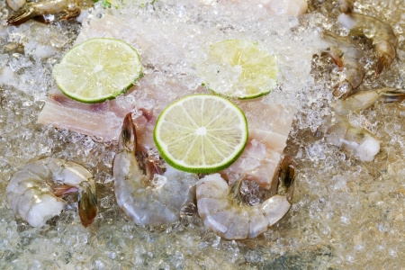 Closeup horizontal photo of fresh raw white fish, shrimp, lime slices and crushed ices on top with natural stone underneath as background
