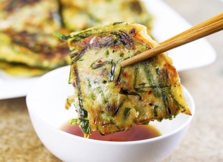 Horizontal photo of Korean Green Onion Pancake being held with chopsticks while be dipped into small cup of sauce in front of plate filled with more pancakes Stock Photo