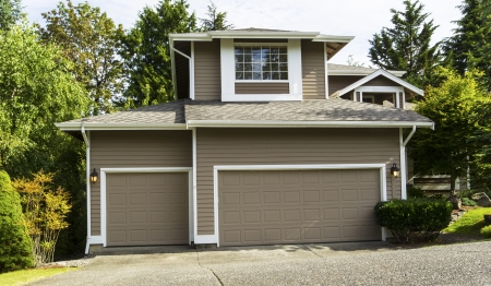 single family home: Front horizontal view of a Northwest American home with three car garage within the Northwest section of United States in the suburbs Stock Photo