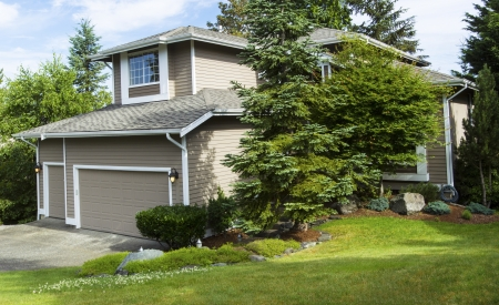 Horizontal photo of a Northwest American home surrounded by large evergreen trees, green grass, and flower bed within the Northwest section of United States in the suburbs  Stock Photo - 21122707