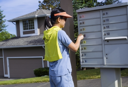 Horizontal photo of a mature woman checking her mailbox with a Northwest American home in the background  photo