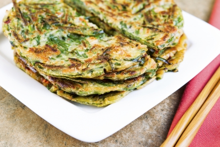 Horizontal photo of stacked Korean green onion pancakes in plate, chopsticks on cloth napkin with stone table underneath