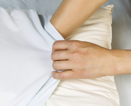 case sheet: Female hands pulling pillow case over pillow with bed sheets in background