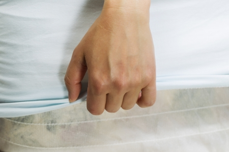 Horizontal female hand pulling bed sheet with mattress and box spring in background  Stockfoto