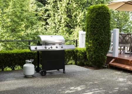 grill: Horizontal photo of a large barbeque cooker on concrete outdoor patio with woods and deck in background