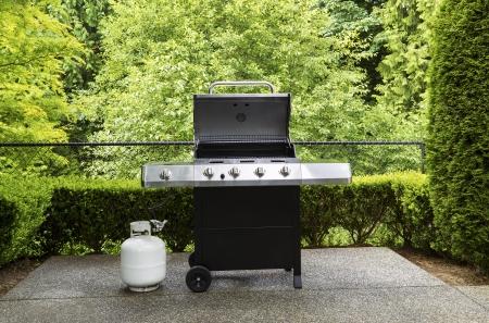 森の中の背景を持つコンクリートの屋外パティオ、ふた付きの大規模なバーベキュー炊飯器の水平方向の写真