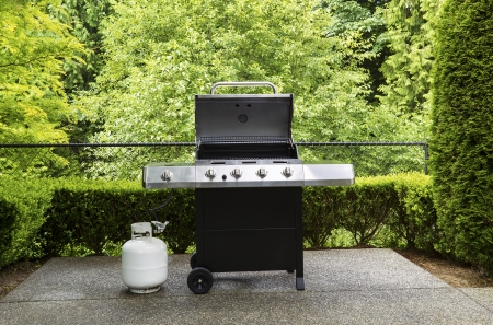 grill: Horizontal photo of large barbeque cooker, with lid up, on concrete outdoor patio with woods background