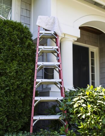 Vertical photo of ladder with paint and brush leaning against house in background
