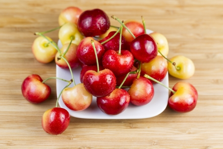 Horizontal photo of Rainier cherries, with water drops, in white dish on natural bamboo board