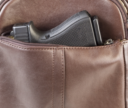 weapons: Photo of modern personal weapon in woman brown leather handbag Stock Photo