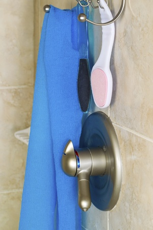 shower stall: Vertical photo of shower accessories consisting of wash cloth, scrubbers, hanging basket, faucet with shower wall in background