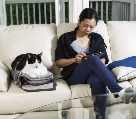 Photo of mature woman and family cat resting on living room couch with large windows in background photo