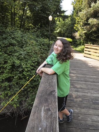 freshwater: Vertical photo of young girl, looking forward, fishing off of wooden bridge for trout with stream, walk path and trees in background