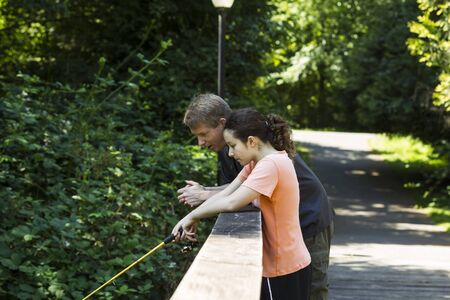 Horizontal photo of young girl and her father fishing off wooden bridge with trees and lamp post in background