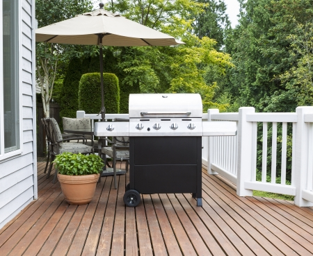patio chair: Photo of large barbecue cooker on cedar deck with patio furniture and trees in background