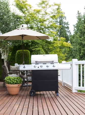 Vertical photo of large barbecue cooker on cedar deck with patio furniture and trees in background